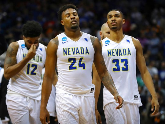Nevada's Elijah Foster, Jordan Caroline, and Josh Hall, from left, walk off the court after the team's 69-68 loss to Loyola-Chicago during an NCAA men's college basketball tournament regional semifinal Thursday, March 22, 2018, in Atlanta.