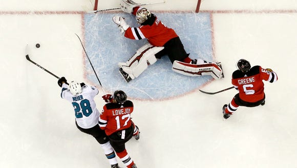 New Jersey Devils goalie Keith Kinkaid, center, dives