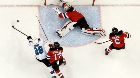 New Jersey Devils goalie Keith Kinkaid, center, dives to defend the net as San Jose Sharks right wing Timo Meier (28), of Switzerland, tries to get a shot during the period of an NHL hockey game, Friday, Oct. 20, 2017, in Newark, N.J Devils' Ben Lovejoy (12) and Andy Greene (6) defend on the play. The Sharks won 3-0. (AP Photo/Julio Cortez)