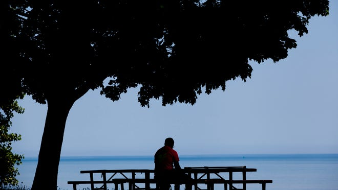 A man relaxes at a picnic table while reading a book Thursday at Lakeside Park in Port Huron. The first phase of renovations at the park starts in September.