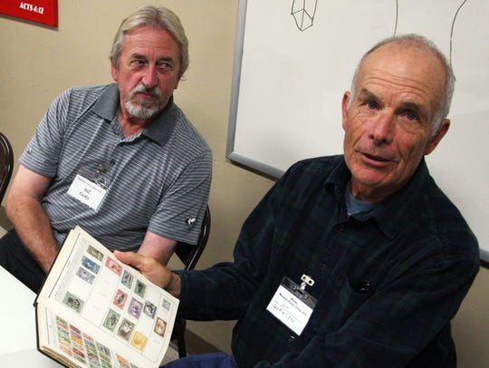 Stamp Club member Jim Dirksen, right, shows a collection