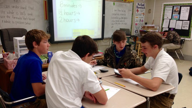 """Oak Hill High eighth-graders in April Durand's class work through problems in groups of four on Tuesday. Students are expected to talk through the problems in their group. They can ask Durand questions but only after first asking their partners. Durand uses PARCC-like problems as daily """"bell ringers"""" to give students an idea of what to expect on the state standardized test to be administered starting March 16."""