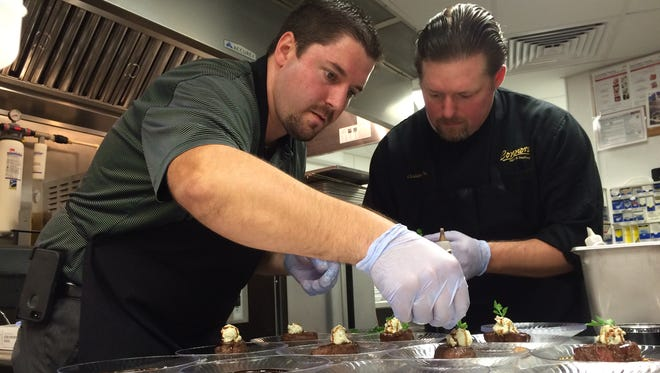 Managing partner Matt Williams, left, and assistant manager Christian Fuller of Connors Steak & Seafood at Gulf Coast Town Center assemble plates of steaks for the Best of Taste judging held at JetBlue Park in southeast Fort Myers last week in advance of Sunday's Taste of the Town event.