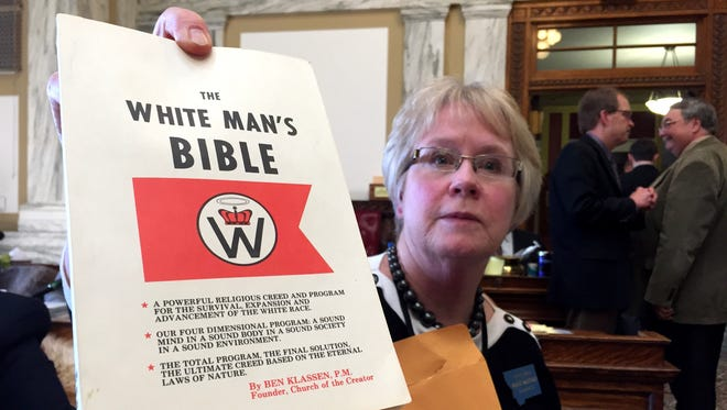 """Rep. Margie MacDonald, D-Billings, holds a copy of the """"White Man's Bible"""" by Ben Klassen, founder of the Church of the Creator and advocate for racial holy war. A proposed bill to put before the voters a constitutional amendment about religious freedom would have the unintended consequence of legitimizing even the most hateful of religious beliefs, such as those held by hate groups, MacDonald told the Montana House of Representatives during debate Friday."""