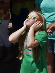 Coralie Lawrence uses a set of solar eclipse viewers to look at the sun Monday at the Donald W. Reynolds Library in Mountain Home.