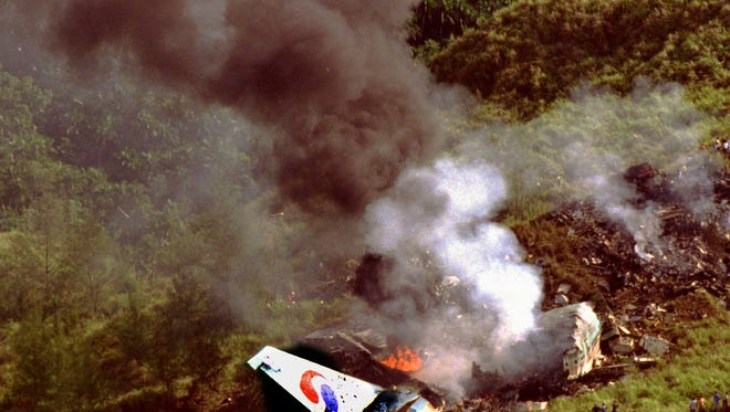 Smoke billows from the wreckage of Korean Air-flight 801 taken hours after the Aug. 6, 1997, pre-dawn crash on Nimitz Hill.