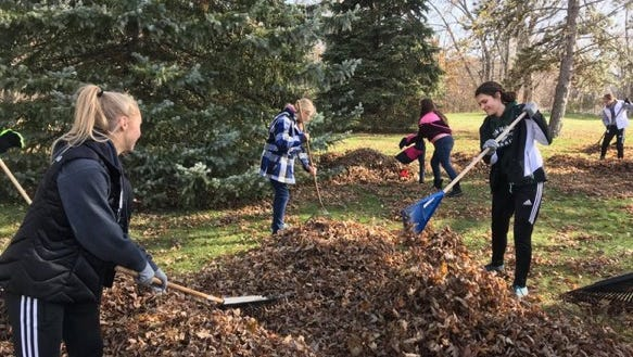 Eighth grade students from Oak Harbor High School rake leaves as part of a community service day.