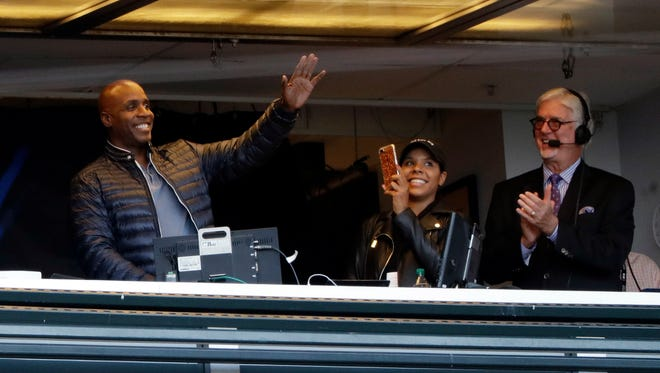 Former Giants player Barry Bonds, left, waves to fans from the broadcast booth.