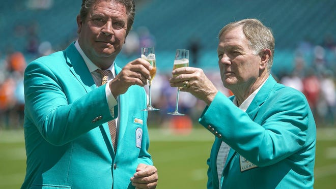 Dan Marino and Bob Griese share a glass of champagne for a spot on CBS before a game vs. the Ravens in September. (BILL INGRAM/palmbeachpost.com