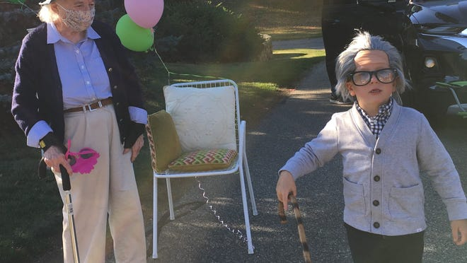 Topsfield resident Janet Brown  and her great grandson Davis wait for the rolling parade to come by her house at Great Hill Friday, Oct. 9., the day she turned 100. Davis dressed up for the occasion and entertained the crowd while they waited.