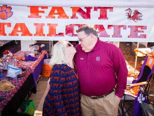 "Clemson alum Ginger Fant and her husband, USC alum Scott Fant, share a kiss at the Clemson vs. USC tailgate on Saturday, November 26, 2016 at Clemson. ""I fell in love with him before I knew he was a damn gamecock,"" says Ginger. The couple has season tickets for both school's football games."