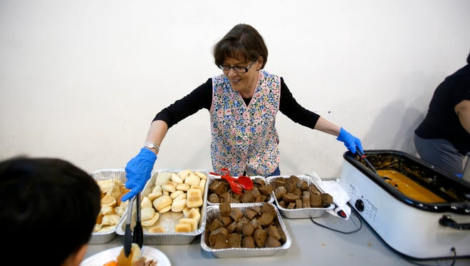 Marjorie Jones, of Aztec, serves rolls and sweet potatoes on Tuesday during a Thanksgiving dinner at the Sycamore Park Community Center in Farmington. Other Thanksgiving dinners are planned Thursday in Farmington, Aztec and Bloomfield.