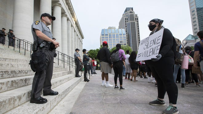 A protester stands opposite an Ohio State Highway patrolman on the Ohio Statehouse steps during a George Floyd protest in Columbus on Wednesday, June 3, 2020.