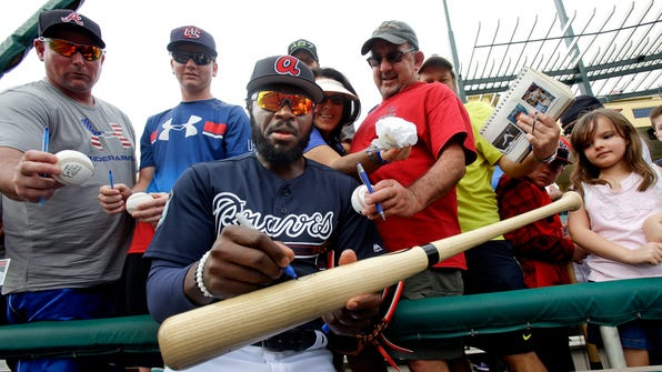 Atlanta Braves infielder Brandon Phillips, front center, signs a bat for a fan at a spring training baseball workout ,Tuesday, Feb. 21, 2017, in Kissimmee, Fla. (AP Photo/John Raoux)