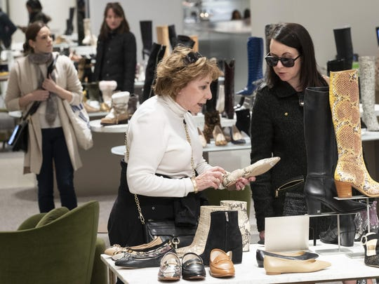 """In this Tuesday, Nov. 26, 2019, photo shows customers shopping in the shoe department at the Nordstrom NYC Flagship in New York. """"Clearly, shopping is much more about an experience,"""" said Jamie Nordstrom, president of Nordstrom stores and the great-grandson of the company's founder."""