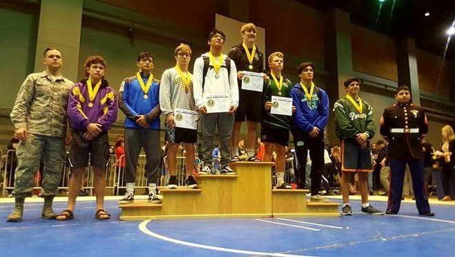 Carlsbad Cavemen wrestler Mario Carrasco at the medals stand with his 6th place medal.