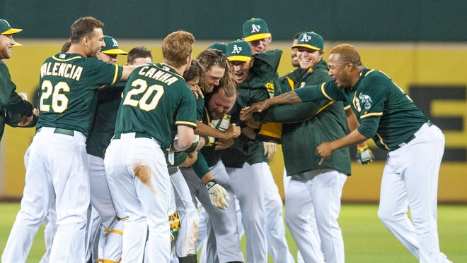 Aug. 18: Oakland Athletics teammates celebrate with designated hitter Billy Butler after he hit a walk-off double against the Los Angeles Dodgers during the tenth inning