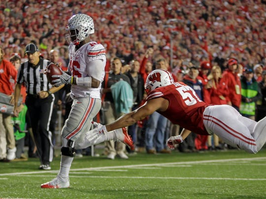 Ohio State quarterback J.T. Barrett, left, scores a touchdown against Wisconsin's Alec James (57) during the second half of an NCAA college football game Saturday, Oct. 15, 2016, in Madison, Wis. Ohio State won 30-23 in overtime. (AP Photo/Andy Manis)