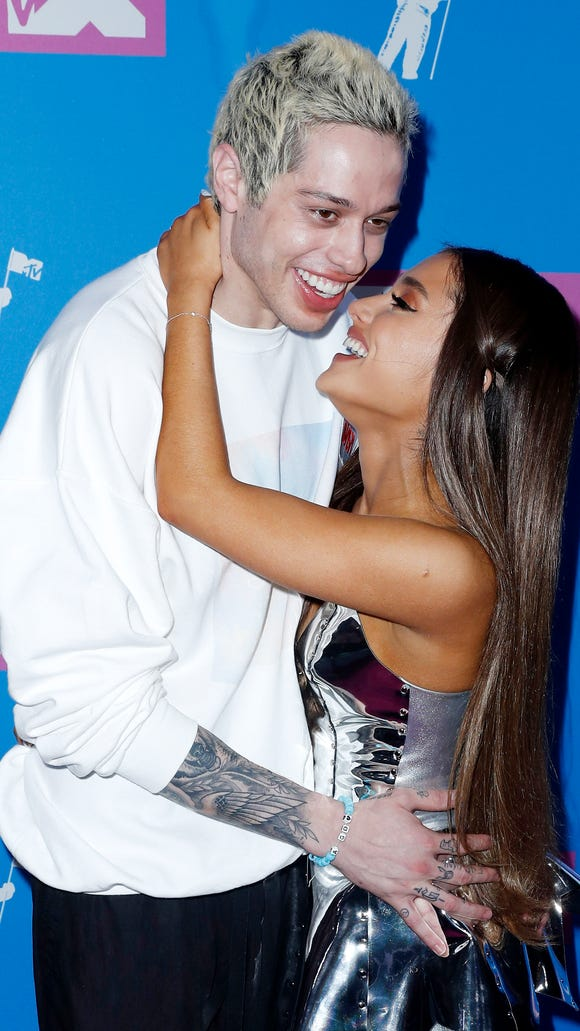 Engaged couple Ariana Grande and Pete Davidson canoodle on the carpet at the VMAs.