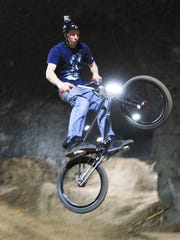 Jeff Perkins, a course designer and builder, demonstrates dirt jumping at a new course being built inside the Mega Caverns. November 25, 2014