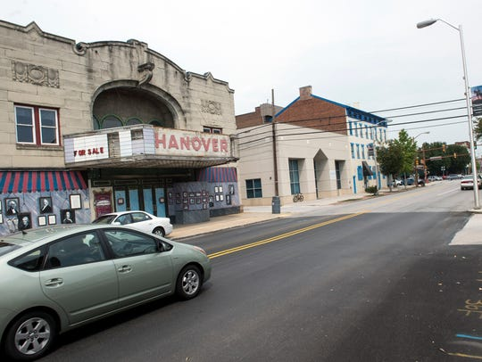A car passes in front of the vacant Hanover Theater.