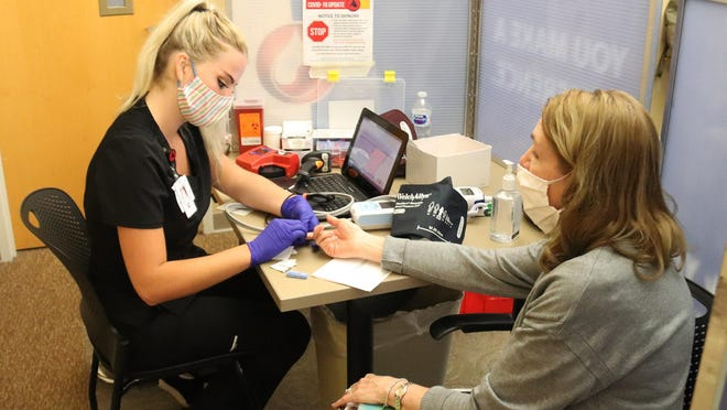 Community Relations Coordinator for OSF Saint James-John W. Albrecht Medical Center Pam Meiner gets her blood typed while going through preparations to donate blood Friday. Doing the screening is Charity Braford of Mississippi Valley Regional Blood Center.