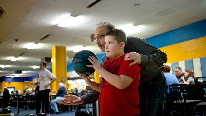 Trent Markle, 9, of Port Huron, gets pointers from his grandfather Jim Hawrys while they bowl together Wednesday, Dec. 30, 2015 at Port Huron Lanes.