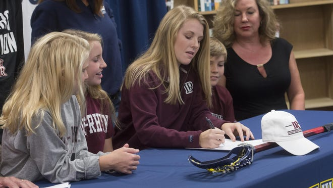 Gulf Breeze High School's Frances Williams, center, signs lacrosse scholarship with Lenoir-Rhyne University in Hickory, N.C. .