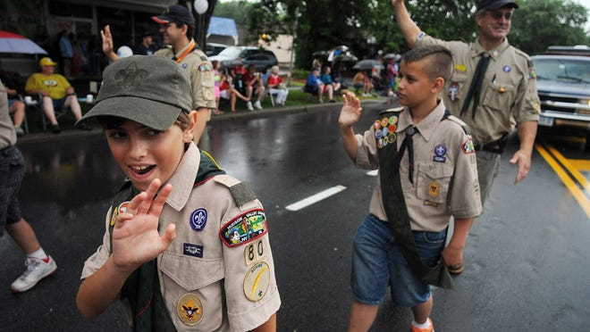 Boy Scout Troop 80 Tenderfoot Christian Faber, left, waves during the Hyde Park Independence Day Parade on Friday. At right are First Class Scout Kyle Mulkins and Scoutmaster Craig Burke. Troop 80 is based in Hyde Park
