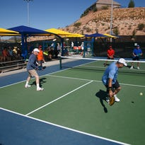 Dave Davidson, left, and his doubles partner Greg Conn both reach to return a shot from their opponents Dewayne Ichiriu, far right, and Scott Hickman, far left, during Huntsman World Senior Games pickleball action at the Little Valley Pickleball Courts in St. George, Monday, Oct. 12, 2015.