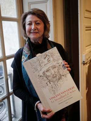 """Art historian and Van Gogh specialist Bogomila Welsh-Ovcharov poses with the book """" Vincent Van Gogh The lost Arles Sketchbook"""", during a press conference held in Paris, France, Tuesday, Nov. 15, 2016. Art experts are disagreeing as to whether a book of previously unpublished drawings reported to be by Dutch master Vincent Van Gogh is authentic or fake."""