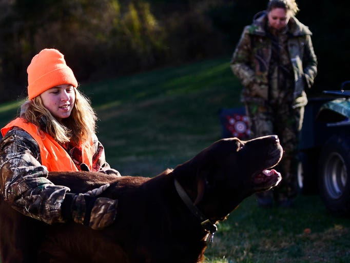 Taylor Howell pets her grandparents' dog, Gunner, after