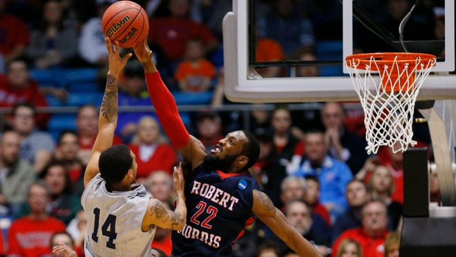 Robert Morris Colonials guard Lucky Jones (22) blocks a shot by North Florida Ospreys guard Dallas Moore (14) during the second half in the first round of the 2015 NCAA Tournament at UD Arena. Robert Morris won 81-77.