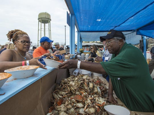 FILE IMAGE: Longtime volunteer Cliff Horsey serves up crabs to ECI employee Pamela Trower of Princess Anne..