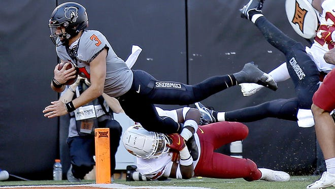 Oklahoma State quarterback Spencer Sanders, left, dives for a touchdown over Iowa State defensive back Isheem Young in the third quarter at Boone Pickens Stadium on Saturday. OSU won 24-21.