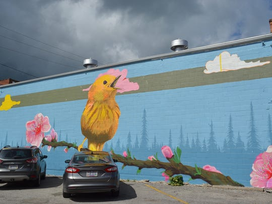 Matt Ritter painted a yellow warbler perched on a peach branch, highlighting the importance of birding and the peach industry to the local economy.