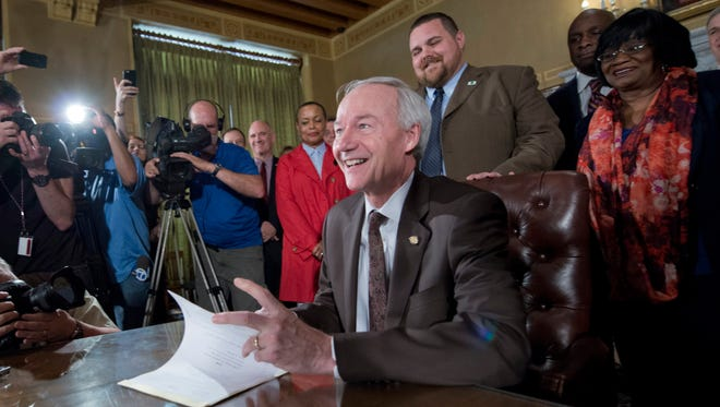 Arkansas Gov. Asa Hutchinson signs a reworked religious freedom bill into law after it passed in the House at the Arkansas state Capitol in Little Rock on Thursday.