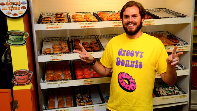 Groovy Donuts owner Andrew Gauthier stands in front a spread of donuts inside of his shop in Williamston.