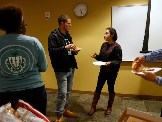 Seniors Hansen Breitling and Mayra Rocha, both with the Ethnic Student Promoters organization, grab some pizza before a meeting Dec. 10, 2015, at the University of Northern Iowa in Cedar Falls. Conversations at UNI and Iowa's other public and private universities have led to a disturbing conclusion: Many black students say they feel isolated and unwelcome on campus.