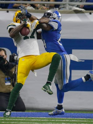 The Packers' Davante Adams grabs a touchdown pass in the fourth quarter with tight coverage from the Lions' Nevin Lawson.