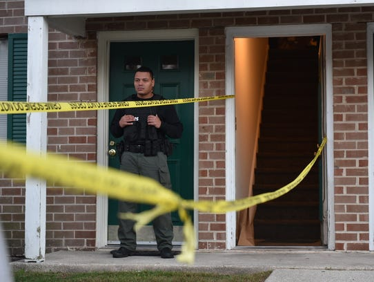 A Vineland police officer stands outside a second-floor