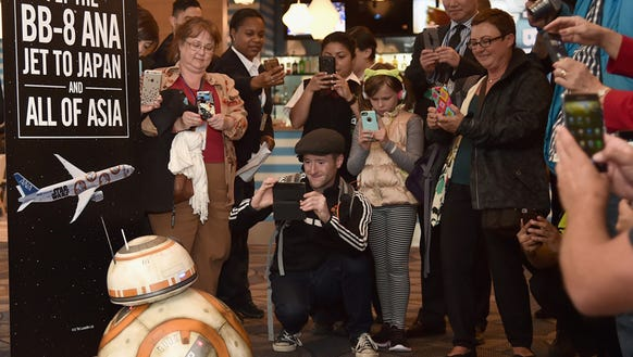 Visitors at LAX check-out a model of Star Wars droid