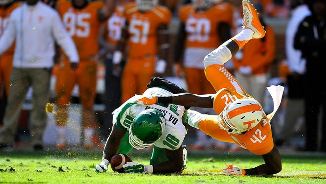 North Texas quarterback DaMarcus Smith (10) kicks up turf as he slips and is the sacked by Tennessee defensive lineman Chris Weatherd (42) on  Nov. 14, 2015.