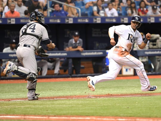 Tampa Bay Rays right fielder Carlos Gomez (27) gets tagged out by New York Yankees catcher Gary Sanchez (24) during the fourth inning at Tropicana Field.