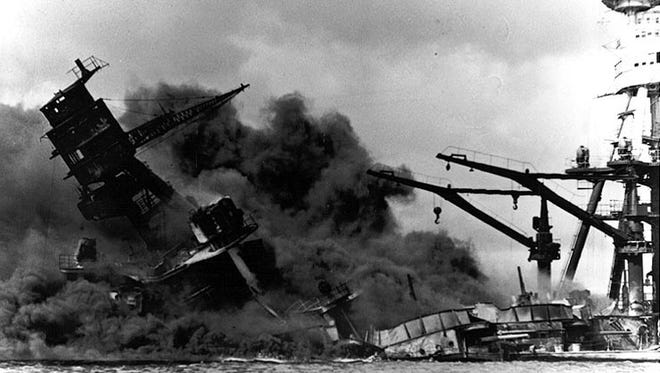 Photo #: NH 97380  Pearl Harbor Attack, 7 December 1941  The forward superstructure and midships gun positions of the sunken USS Arizona (BB-39), afire after the Japanese raid, 7 December 1941. At right are the ship's mainmast and boat cranes, which were beyond the areas wrecked by the explosion of her forward magazines.  Official U.S. Navy Photograph, NHHC collection.  Online Image: 82KB; 740 x 595