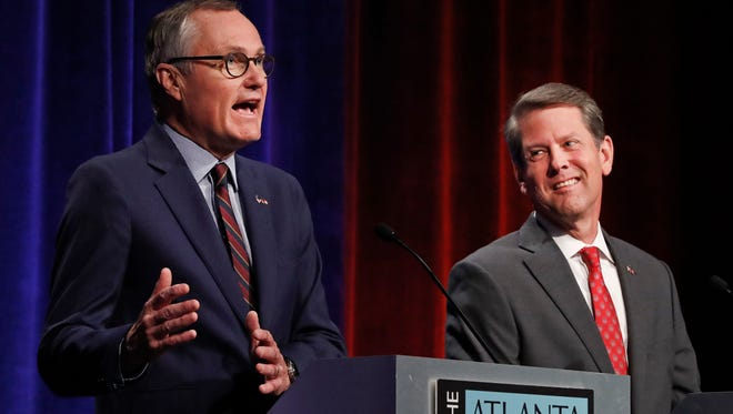 In this July 12, 2018, photo, Republican candidates for Georgia Governor, Lt. Gov. Casey Cagle, left, and Georgia Secretary of State Brian Kemp speak during an Atlanta Press Club debate at Georgia Public Television  in Atlanta. The two will face each other July 24 in a runoff election for the Republican nomination.