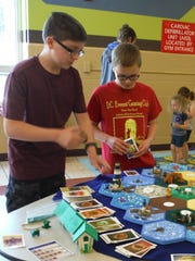 Students play Settlers of Catan at the Gaming with Khiana event.
