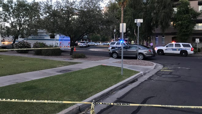 Police crime tape surrounds an area near First Avenue and Roosevelt Street after an officer-involved shooting Monday.