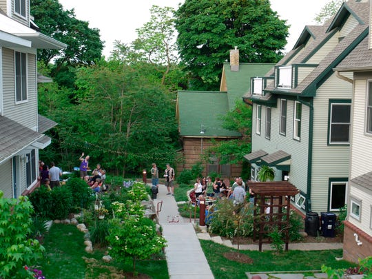 This undated photo provided by Joanna Vander Plaats shows residents of Newberry Place Cohousing Community in Grand Rapids, Mich. Cohousing developments are designed to foster interaction between neighbors. The developments are generally built to be pedestrian-friendly with parking out of view. Front Porches face each other so neighbors can more easily talk. (Joanna Vander Plaats via AP)