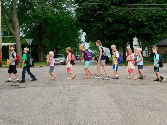 This undated photo provided by Joanna Vander Plaats shows children of the  Newberry Place Cohousing Community walking together to a neighborhood elementary school on the first day of the year in Grand Rapids, Mich. Cohousing developments are designed to foster interaction between neighbors. (Joanna Vander Plaats via AP)
